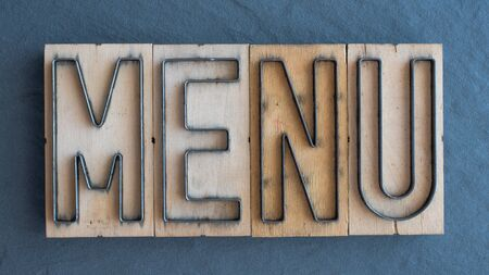 Old wood and steel number plate dies spell out the word MENU