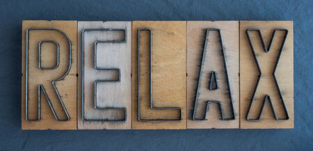 Old wood and steel number plate dies spell out the word RELAX Banco de Imagens