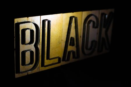Old wood and steel number plate dies spell out the word BLACK