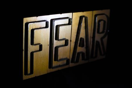 Old wood and steel number plate dies spell out the word FEAR
