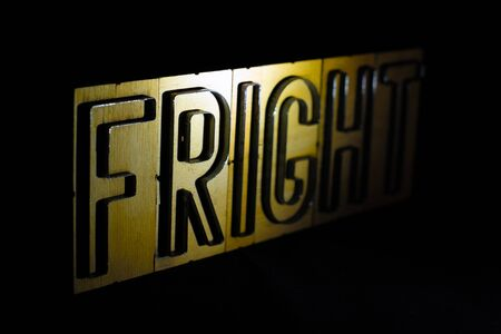 Old wood and steel number plate dies spell out the word FRIGHT Banco de Imagens