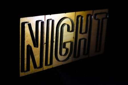 Old wood and steel number plate dies spell out the word NIGHT