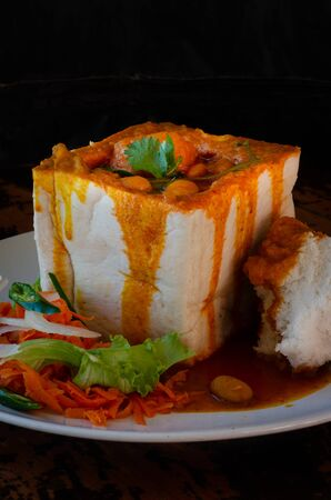 A Durban Bunny Chow - or, in this case, a vegerarian quarter bean bunny - served with sambals. This is an iconic Durban meal consisting of a section of a loaf of bread hollowed out and filled with bean curry and gravy. The sambals are grated carrot with chopped chilli. The meal is traditionally eaten with ones fingers.