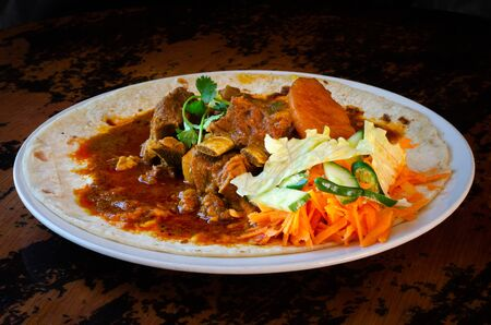 A mutton curry roti with sambals - an iconic Durban meal consisting of a roti topped with mutton curry and gravy. The sambals are grated carrot with chopped chilli.