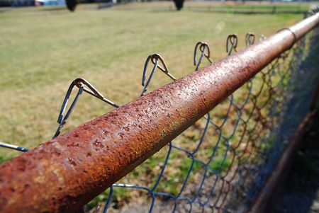 Close up of a chained link fence rail.