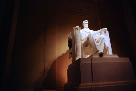A night time picture of Abraham Lincoln in his chair at the Lincoln Memorial.