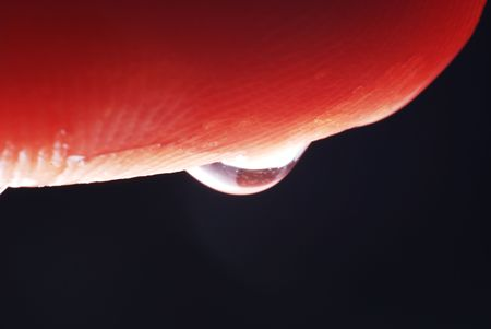 a drop of water clinging to the bottom of a finger.