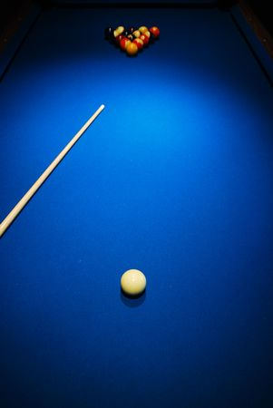 cue stick: A pool table with a cue stick and balls.
