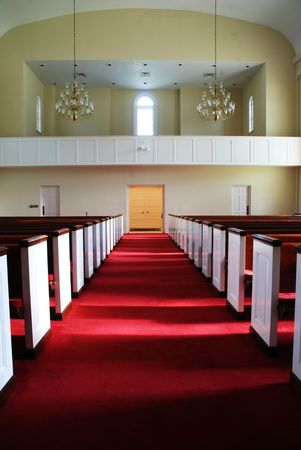 pews: A church aisle with empty pews and carpet in red. Stock Photo