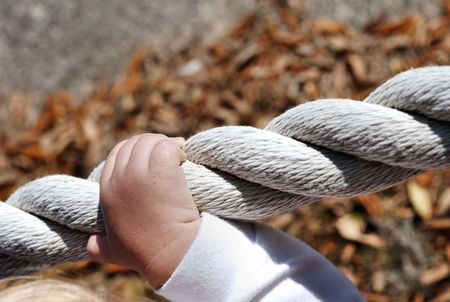 A child\'\'s hand gripping onto a rope boundary.