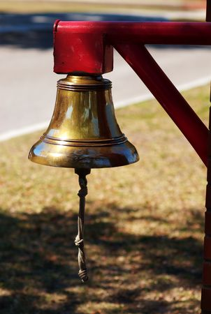 suppertime: A brass bell on a red post with rope hanging down. Stock Photo