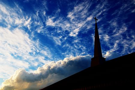 A church steeple in a cloudy sky at sunset.