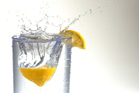 A lemon half splashing into a glass of water. Stock fotó