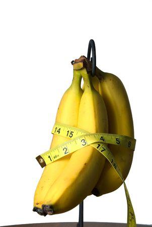 Measuring tape around a bunch of Bananas. photo