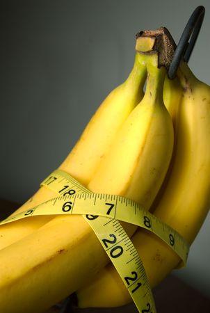 Measureing tape around some bananas. photo