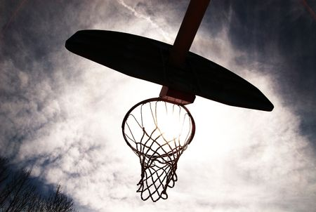 Basketball hoop shot from underneath. Backlit with sun coming through. photo
