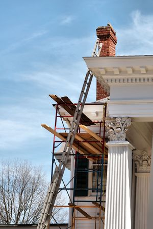 chimneys: A white house being painted and reconstructed.