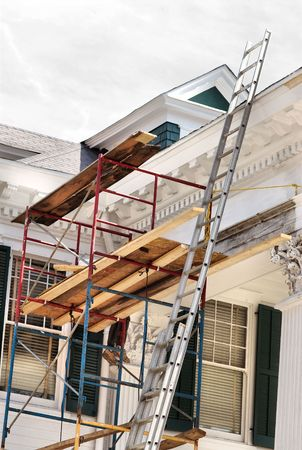 home repairs: A white house being painted and reconstructed.