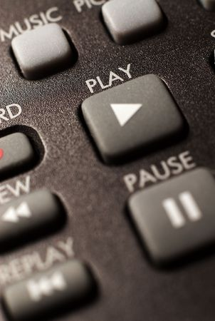 pause button: A closeup of a remote control focusing on the play button. Stock Photo