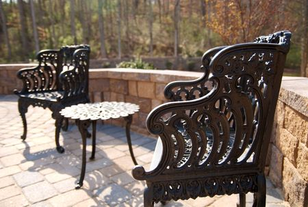 A couple of Cast-iron chairs on a patio. photo