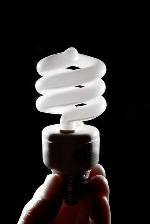 Human hand holding cfl lightbulb Stock Photo