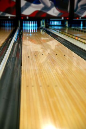 A bowling alley lane with narrow depth of field focusing in the middle on the arrows.