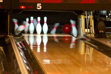 Bowling pins being knocked  down at an alley by a a ball.  Slow shutter speed.
