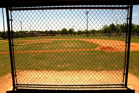 baseball dugout: chain link fence in the dugout on a baseball field. Stock Photo