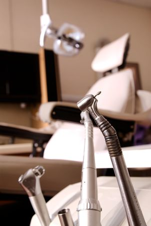 dentist drill: A dentist drill and tools in foregroundwith dentists chair in background with light. Stock Photo
