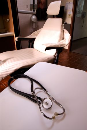palpitations: A stethoscope on a white table with medical dentists chair in background.