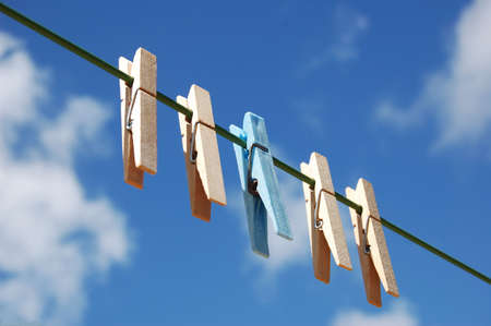 distinct: cloth pegs with a under the sky . A blue peg distinct from the other.
