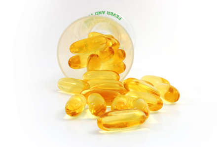 fish oil +evening primrose oil caplets spilling out from the cup .