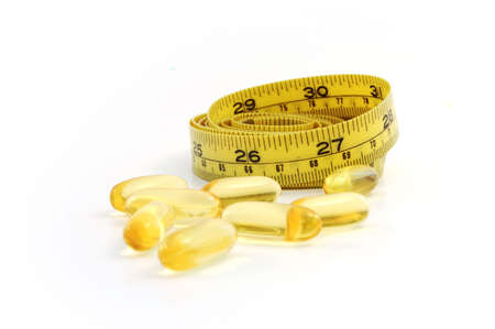 diet and supplement. yellow measuring tape and fish oil caplets