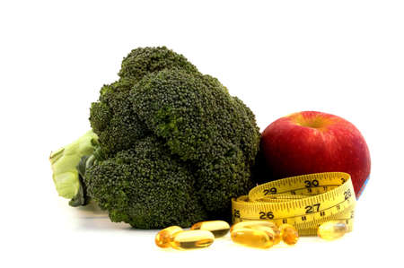 Apple, broccoli,fish oil caplets and measure tape