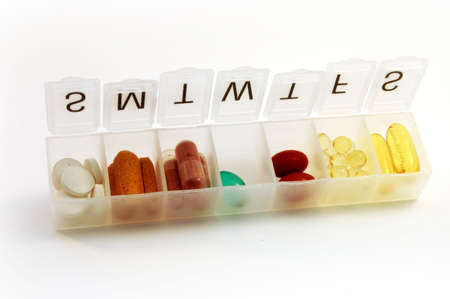 Pill box filled with variety of pills and supplement.