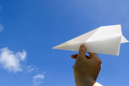 Hand throwing the paper airplane to the air Stock Photo