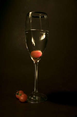 Tomato inside the glass in dark background . Lit from the left side