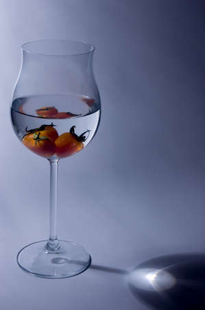 Soft siding light illuminating the wine glass with tomato inside the glass photo