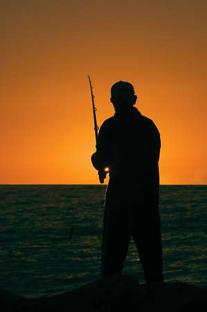 Silhouette of a fisherman as the sun sets on cottesloe beach , Perth Stock Photo