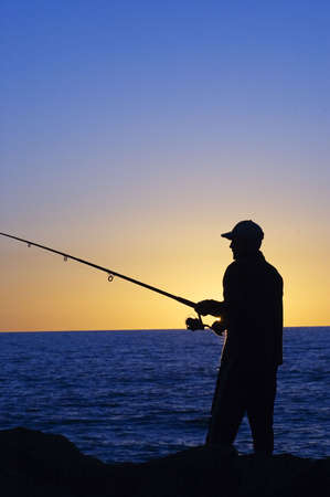 fisher animal: Silhouette of Fisherman at sunset at Cottesloe beach , Perth