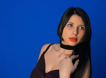 Model with big breasts and red lips posing in the studio