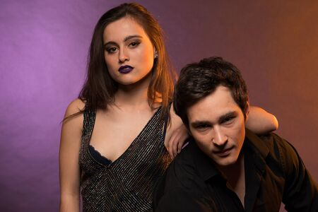 Couple of models posing together in the studio with colored lighting