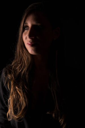 Model with black dress photographed with specific lights and shadows
