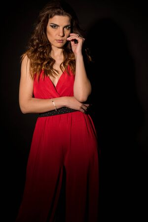 Model posing in the studio with black background and a nice red dress 写真素材