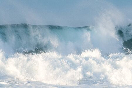 Surfer swallowed by a big wave on a beach on the north coast of Spain Stock Photo