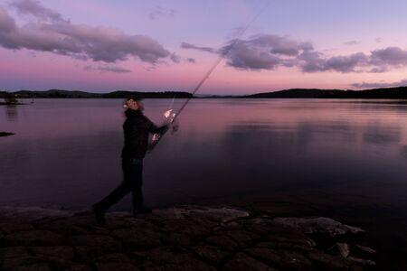 Self Portrait Fishing at Dusk in a Lake 版權商用圖片