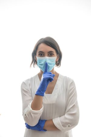 Woman with white shirt, blue gloves and mask, asking for silence for the covid19. With white background. Horizontal photo. 版權商用圖片