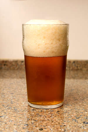 A very well poured beer in a glass, with just the right foam Imagens