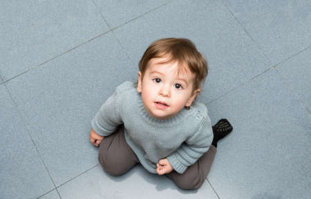 An approximately one-year-old baby kneeling on the kitchen floor, looking at me and smiling Banque d'images