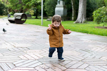 A year and a half old baby taking his first steps in the park